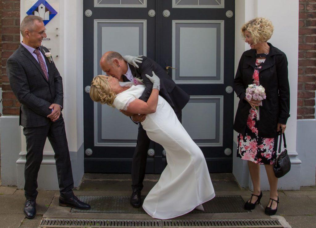 Küssendes Brautpaar vor Kirchentor © Ulrike Schwägerl